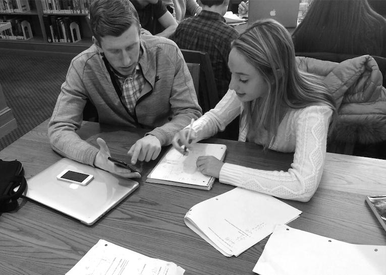 Seniors Tyler Curran and Cate Goldsmith utilize time in the library to study for exams, yet they still have work for the second trimester to complete. Photo by Robert Hallock.