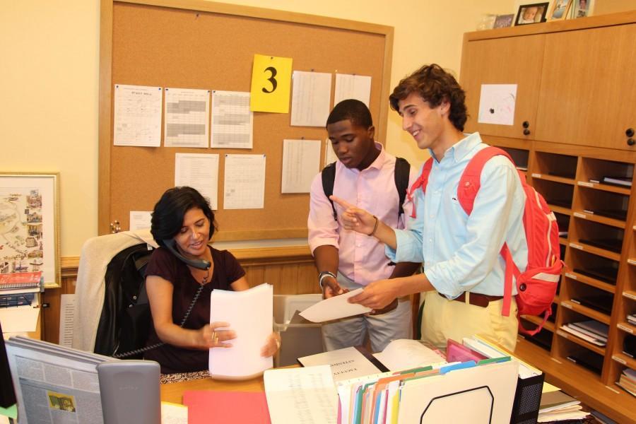 Ms. Coy multitasks, answering the phone while providing seniors Elijah Ngbokoli and TJ Gooley with important documents.