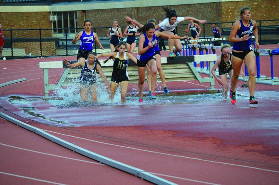 Senior Lindsay Schechter jumps over the wet barrier in the steeplechase at the Suffern Invitational.