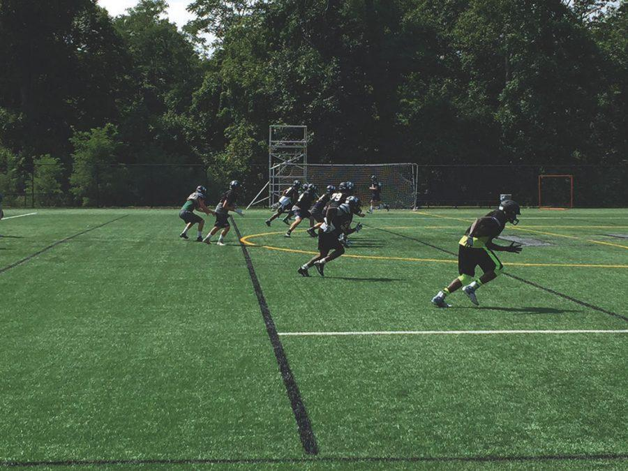 The Football team practices over plays on the turf.