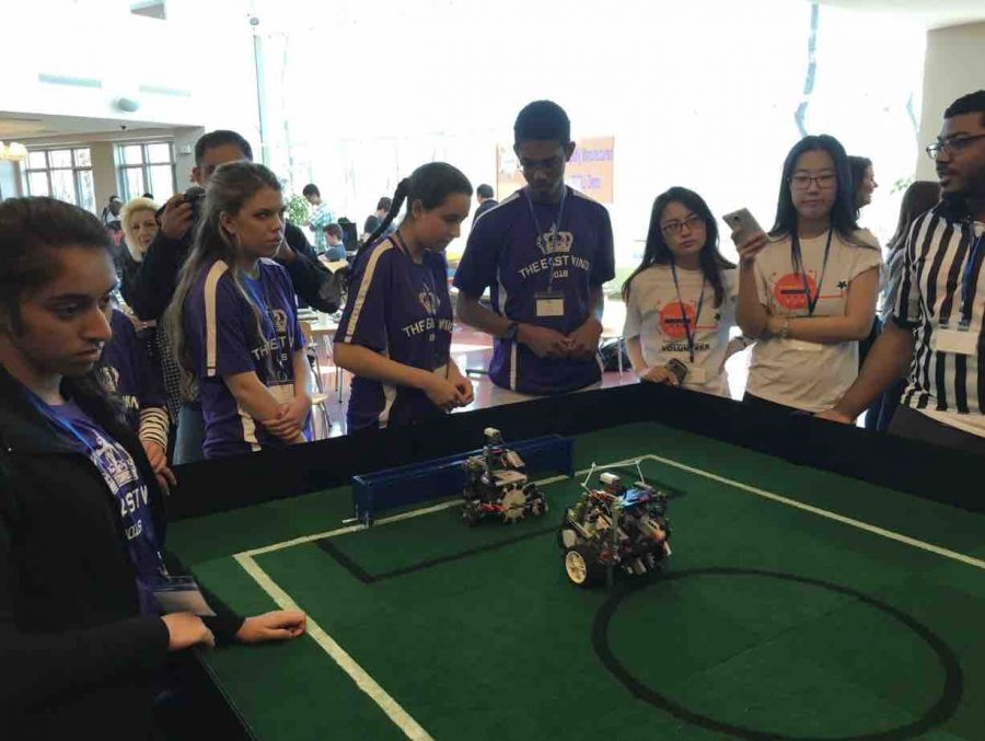 Jasmine (pictured second from the left) works with robots to ensure they are able to play offensive and defensive positions independently in a simulated soccer match.