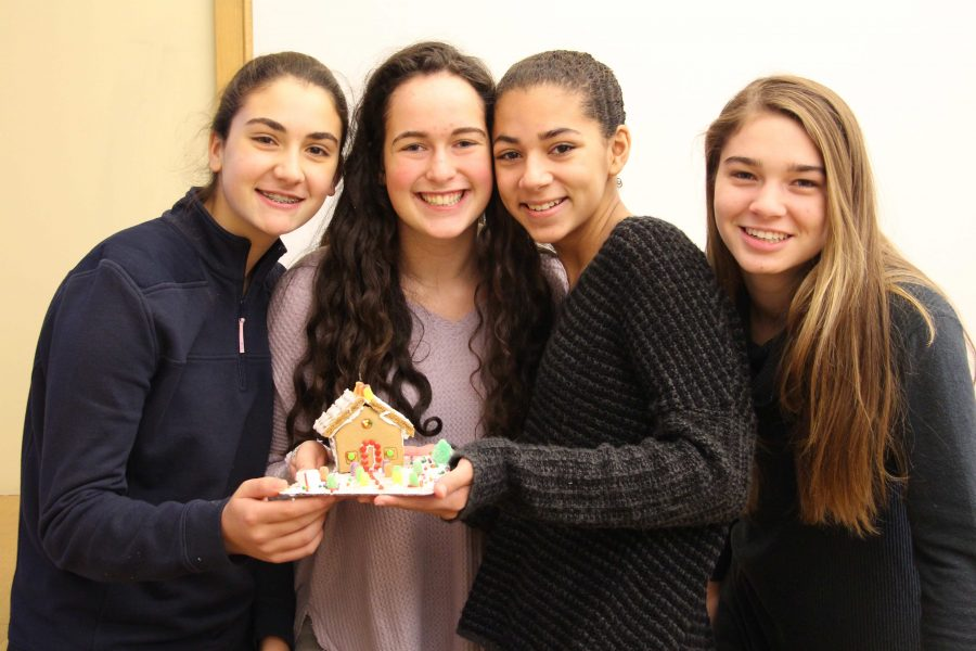 Freshmen Sofia Graziano, Jordan Miller, Ella Jones and Leah Holmes smile after finishing their gingerbread house.