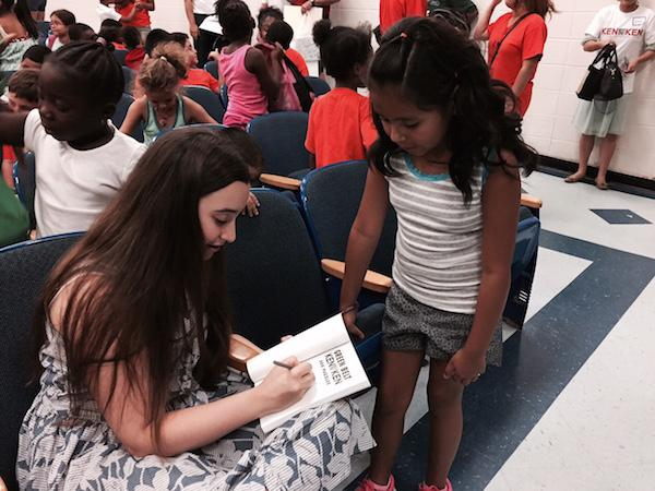 Ellie autographs a KenKen problem book for the winner of a local competition at a White Plains STEM camp.