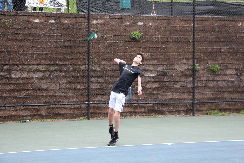Jared Tillis serves the ball during their Horace Mann match.