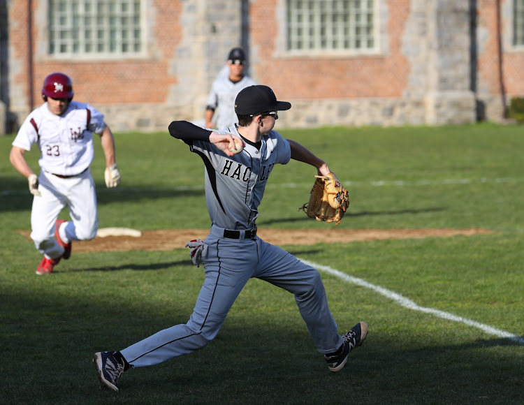 Peter Clyne throws the ball to first base.