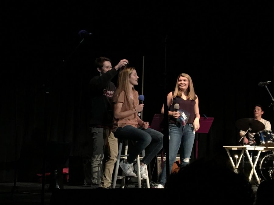 """Sophomore Alexander Goldman play an acoustic version of """"Message in a Bottle"""" by the Police. This year's coffeehouse was hosted by seniors Lilliana Khoshroshahi and Francesca Doctors who offered audience volunteers minute-to-win-it games in between numbers for a chance to crack a raw egg on one of their heads."""