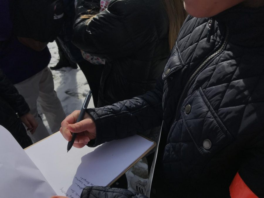 A student signs a petition for a letter directed at policy makers asking for change.