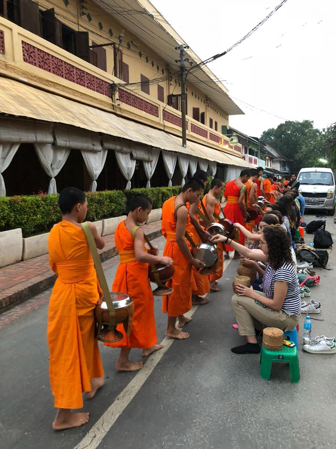 Students participate in the early morning Alms Giving Ceremony in Luang Prabang, Laos. In this ceremony, local Buddhist monks with alms bowls by their sides walk through the streets of Luang Prabang to receive food donations, most commonly steamed rice.