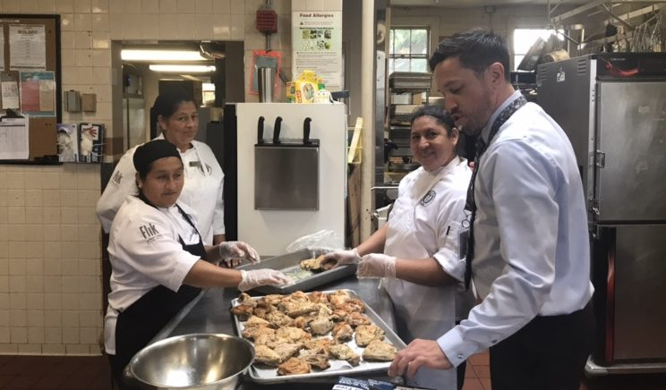Head of Dining Services Michael Collichio inspects a chicken dish with other members of Flik. Collichio is new to Hackley this year. Among other things, he has worked as a line cook and a hospital chef in the past.