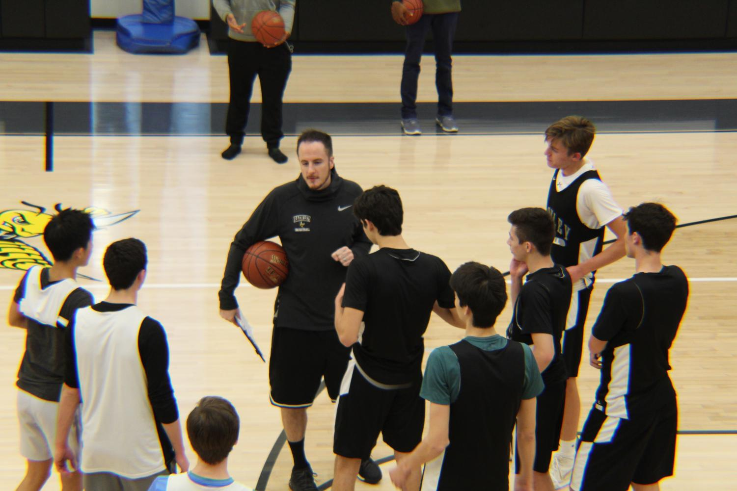Coach Kuba explains a drill to the team. He emphasizes quick ball movement to the team in practice. This is Coach Kuba's first season coaching the boys' varsity basketball team.