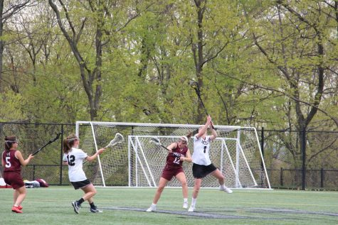 Junior midfielder Julia Thomson reaches to win the draw. Thomson uses her speed and height to her advantage in dominating Horace Mann.