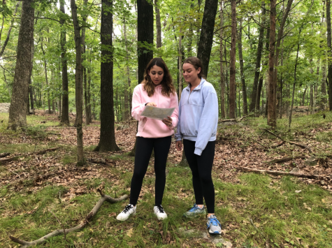 Sophomores Logan Oscher and Hannah Carrey attempt to find the next number of their scavenger using their map of Tea Town. Students were left with only compasses and maps as they explored the woods and looked for the next number in their hunt.