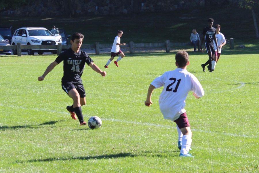 JV Soccer captain Theo Yannuzzi dribbles past defenders in Hackley's game against Horace Mann.