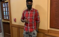Iheukwumere Marcus '22 wears a casual outfit featuring a flannel, pajama pants and slides.