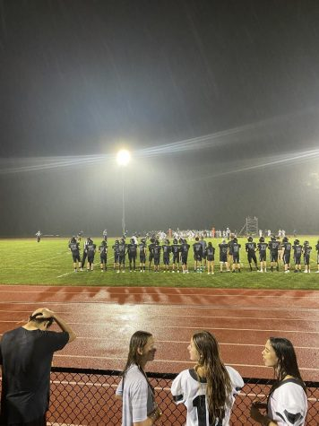 Shortly after crowds gathered for the football game, it started to rain. The chorus was able to sing the national anthem before it began raining.